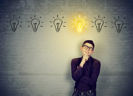 pick: Young happy man leaning on a brick wall looking for best solution idea  Stock Photo