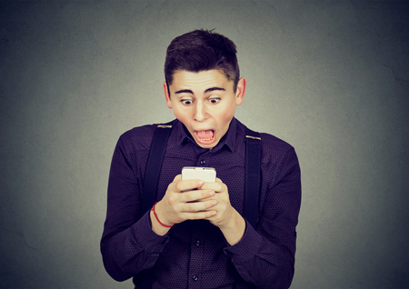 anxious shocked man looking at phone seeing bad news or photos with scared emotion on his face isolated on gray background. Human emotion, reaction, expression Фото со стока