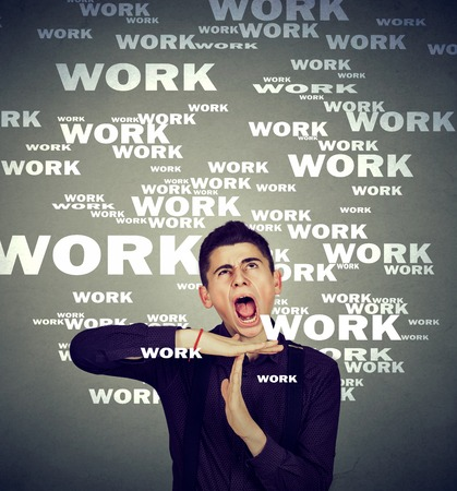 working hours: Stressed man showing time out gesture overwhelmed by long working hours