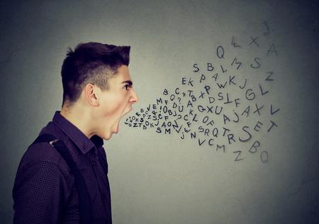 enfado: El hombre enojado gritando con las letras del alfabeto que sale de la boca abierta