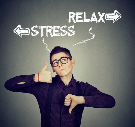 doubtfulness: Stress or relax. Perplexed man with thumbs down thumbs up gesture