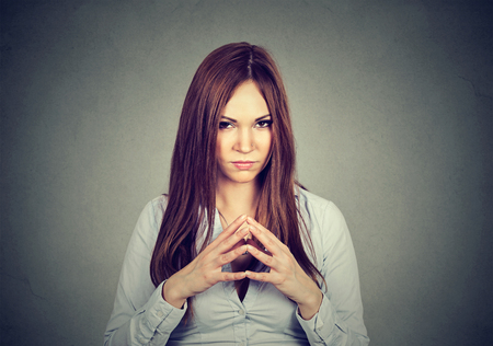Retrato de detalle de astuto, astuto, mujer joven intrigante trazado algo aislado en el fondo gris. emociones humanas negativas, las expresiones faciales, los sentimientos, actitud Foto de archivo