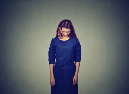 lack of confidence: Sad shy insecure young woman standing looking down avoiding eye contact isolated on gray wall background Stock Photo