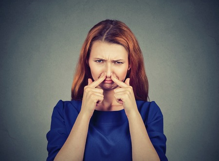 pinches: woman pinches nose with fingers looks with disgust something stinks bad smell isolated on gray wall background. Human face expression body language reaction