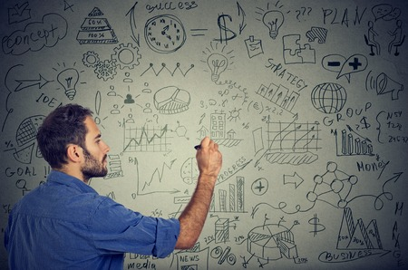 young man writing on the wall business calculations plan