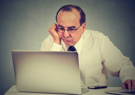 Annoyed bored middle aged man learning how to use computer new technology