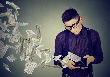 flying man: Sad man looking at his wallet with money dollar banknotes flying out away Stock Photo