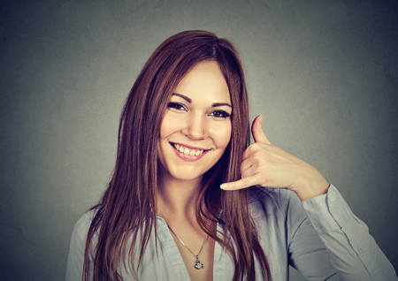 Portrait woman making dial my number sign with hand like phone isolated on gray wall background. Positive human emotion body language