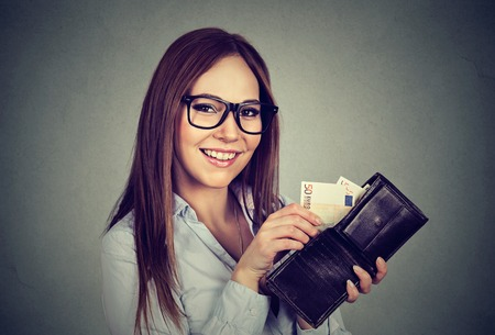 payday: Happy woman taking out money euro banknotes from wallet Stock Photo
