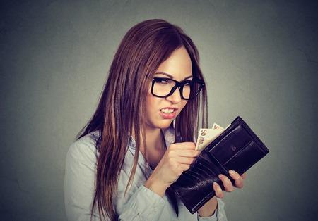 Greedy jeune femme comptage prenant l'argent de son portefeuille Banque d'images - 68416040