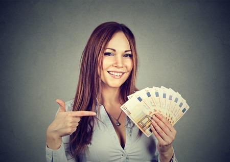 Succesvolle jonge zakenvrouw met geld euro biljetten in de hand geïsoleerd op een grijze achtergrond. Positieve emotie gezichtsuitdrukking. Financieel beloning concept