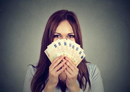 젊은 여자가 유로 돈을 팬 뒤에 그녀의 얼굴을 숨기기 스톡 콘텐츠