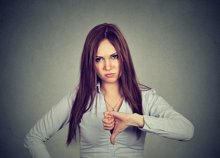 disapproval: Unhappy woman giving thumbs down gesture looking with negative expression and disapproval isolated on gray background