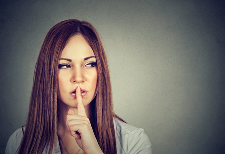 hushed: pretty woman making silence sign isolated over gray background Stock Photo
