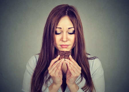 craving: Portrait sad woman tired of diet restrictions craving chocolate isolated on gray wall background. Human emotion. Nutrition concept. Feelings of guilt Stock Photo