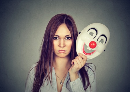 cheerfulness: Portrait young upset worried woman with sad expression taking off clown mask expressing cheerfulness happiness isolated on gray wall background Stock Photo