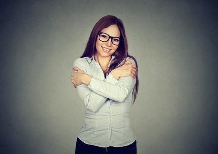 lenguaje corporal: Mujer sonriente que sostiene que se abraza aisladas fondo de la pared gris. emoción humana positiva, expresión facial. Ámate a ti mismo concepto