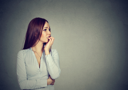 preoccupied: Preoccupied anxious young woman biting her fingernails