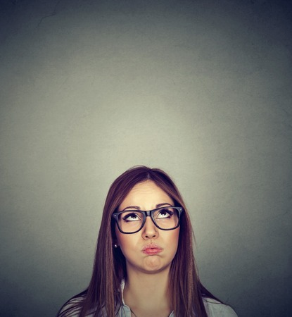 exasperate: Annoyed young skeptical woman looking up isolated on gray wall background with copy space above head. Human emotions, feelings