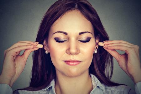 ruido: Control de ruido. Mujer joven con tapones para los oídos aislados sobre fondo gris de la pared Foto de archivo