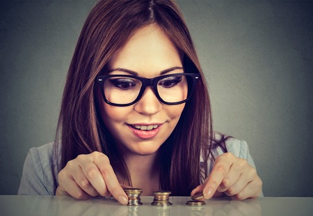 avid: Young woman counting money stacking up coins Stock Photo