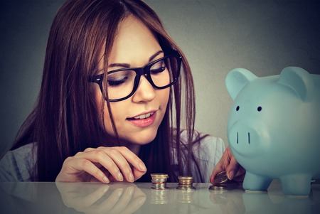 counting money: Young woman counting money stacking up coins Stock Photo