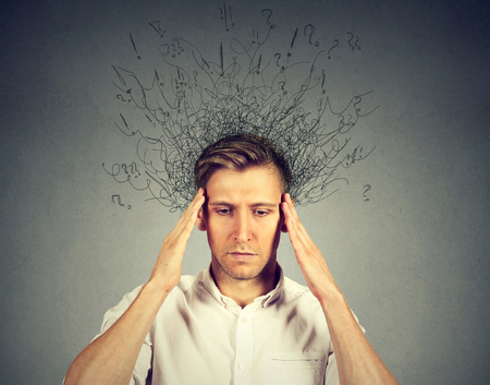 ocd: Closeup sad man with stressed face expression and brain melting into lines question marks. Obsessive compulsive, adhd disorders Stock Photo