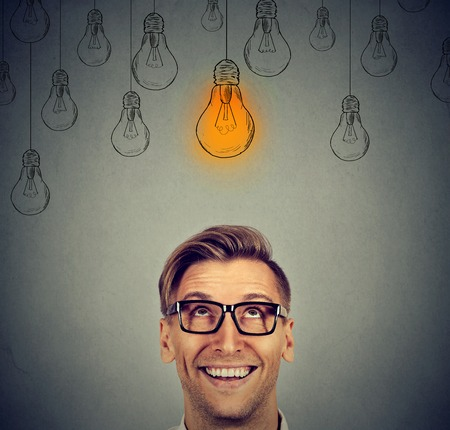 Portrait happy handsome man in glasses looking up at bright idea light bulb above head isolated on gray wall background Фото со стока