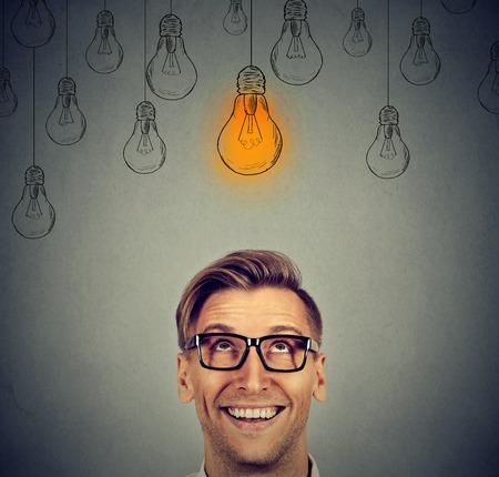Portret gelukkige knappe man in glazen kijken op lumineus idee gloeilamp boven het hoofd geïsoleerd op een grijze muur achtergrond Stockfoto