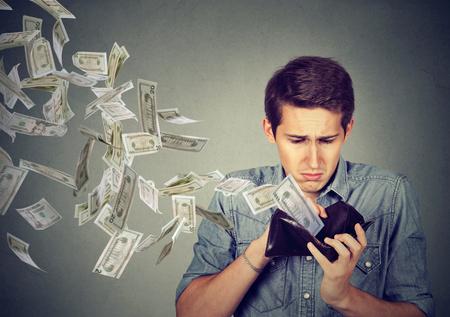 gastos: Homem triste olhando para sua carteira com notas de banco do dólar do dinheiro voando para fora afastado