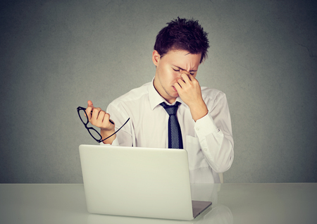 Young tired business man rubbing his eye sitting at table in front of laptop in his office