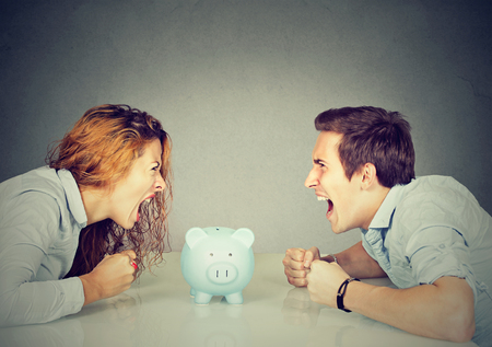 Finances in divorce concept. Wife and husband can not make settlement screaming piggy bank in-between sitting at table looking at each other with hatred