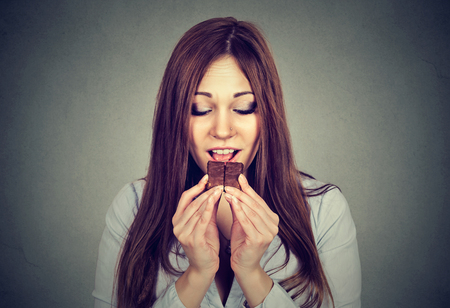 craving: Woman tired of diet restrictions craving chocolate isolated on gray wall background. Human emotion. Nutrition concept. Feelings of guilt