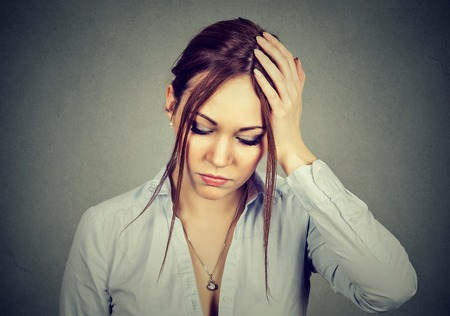desesperado: sad desperate woman with worried stressed face expression looking down