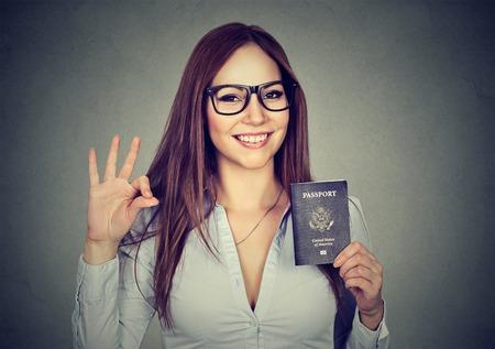 회색 벽 배경에 격리 확인 기호를주는 미국 여권 세로 매력적인 젊은 행복 한 여자. 긍정적 인 인간의 감정. 이민 여행 개념