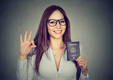 Portrait attractive young happy woman with USA passport giving ok sign isolated on gray wall background. Positive human emotions. Immigration travel concept