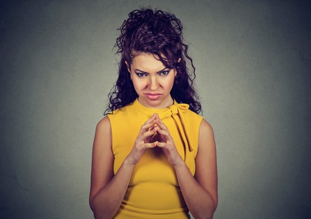 bitchy: Portrait of sly, scheming young woman plotting something isolated on gray background. Negative human emotions, facial expressions, feelings, attitude