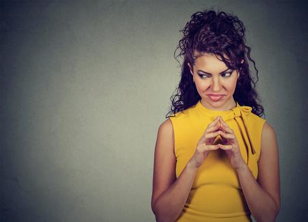 venganza: Sly, mujer joven intrigante tramando algo mirando hacia los lados aislado en fondo gris con el espacio de la copia. emociones humanas negativas, sentimientos, actitud