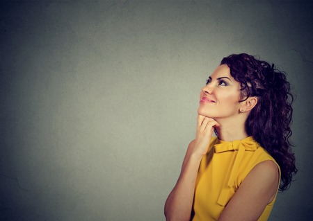feeling happy: Side profile of a happy woman thinking with hand on chin looking up isolated gray wall background with copy space. Positive human emotions, feeling perception Stock Photo
