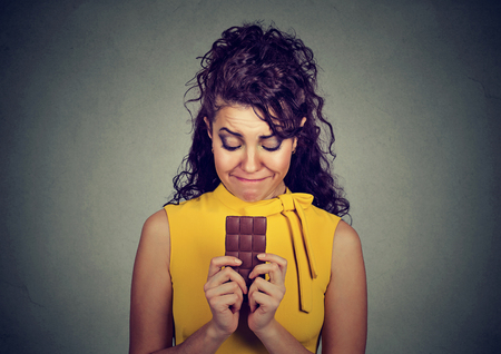 craving: Portrait sad young woman tired of diet restrictions craving sweets chocolate bar isolated on gray wall background. Human emotions. Nutrition concept. Feelings of guilt