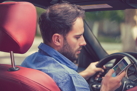reckless: Man using cell phone texting while driving. Risky, reckless driver concept