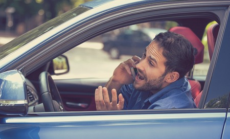 dangerously: Young man talking on mobile phone while dangerously driving car. Risky, reckless driver. Traffic rule violation lack of attention concept. Stock Photo