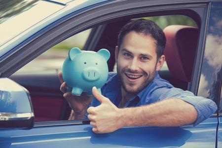 엄지 손가락을 보여주는 돼지 저금통을 들고 그의 새 차 안에 앉아 행복 한 사람