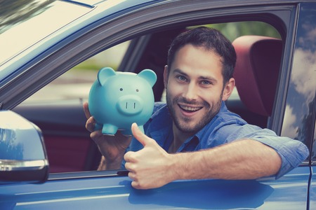 Happy man sitting inside his new car holding piggy bank showing thumbs up Imagens