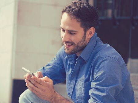 outdoor outside: Happy man texting on phone. Casual urban entrepreneur using smartphone smiling outside office building. Outdoor portrait of modern young guy with mobile in the street sitting on stairs  Stock Photo