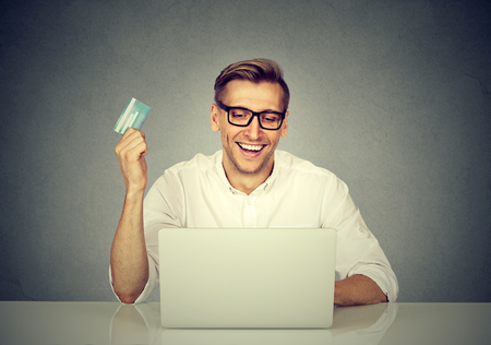cvv: Online shopping and payment. Handsome man showing a credit card and using laptop browsing internet