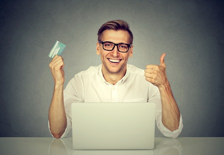 cvv: Online shopping and payment. Handsome man showing a credit card thumbs up while using laptop browsing internet