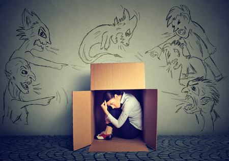 mockery: Bad evil men pointing at stressed woman. Desperate scared businesswoman hiding inside a box isolated on grey wall background. Negative human emotions face expression feelings life perception