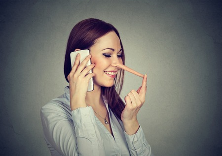 prankster: Happy young woman with long nose talking on mobile phone isolated on gray wall background. Liar concept. Human emotion feelings, character traits Stock Photo
