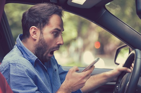 Man sitting inside car with mobile phone in hand texting while driving. Shocked guy checking his smartphone not paying attention at road stunned by bad text message email outdoors background